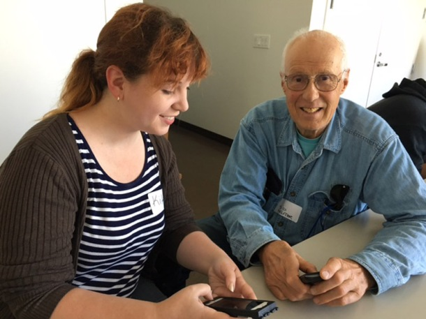 Volunteer helping Next Village SF senior with hand-held device